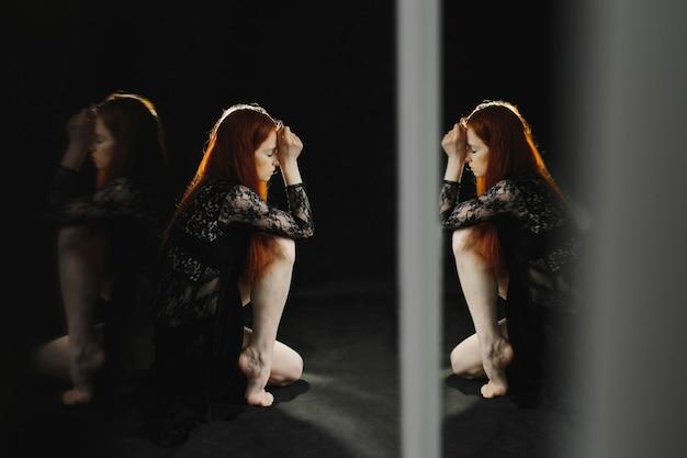 Een aantrekkelijk roodharig meisje in zwarte lingerie zit op de vloer