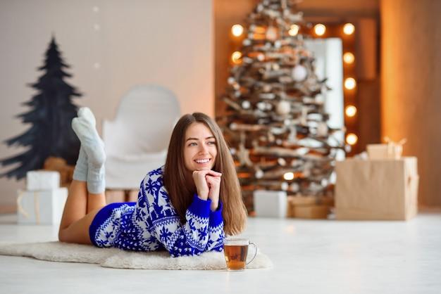 Een aantrekkelijk schattig meisje in een gebreide vakantiesweater ligt op een wit tapijt