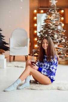 Een aantrekkelijk schattig meisje in een gebreide vakantiesweater zit op een warm wit tapijt met een kop warme thee