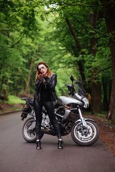 Een aantrekkelijk sexy meisje gekleed in leer poseren in de buurt van een sportmotor buiten