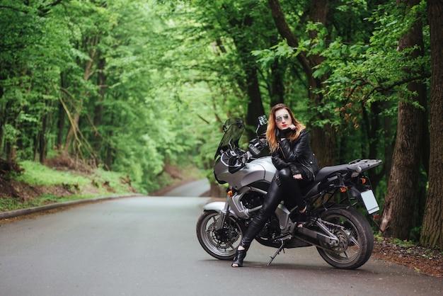 Een aantrekkelijk sexy meisje gekleed in leer poseren in de buurt van een sportmotor buiten Premium Foto