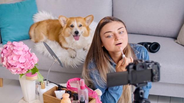 Een aantrekkelijk tienermeisje blogt over make-up. een jong meisje maakt haar beautyvideoblog. een jong meisje doet afstandsonderwijs in cosmetica terwijl ze blogt.