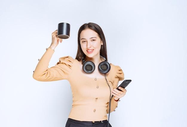 Een aantrekkelijk vrouwenmodel dat een kop met mobiele telefoon en hoofdtelefoons houdt.