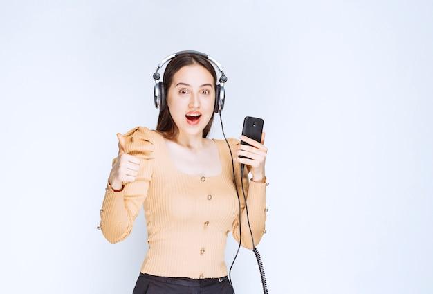 Een aantrekkelijk vrouwenmodel dat muziek in hoofdtelefoons luistert en een duim toont.