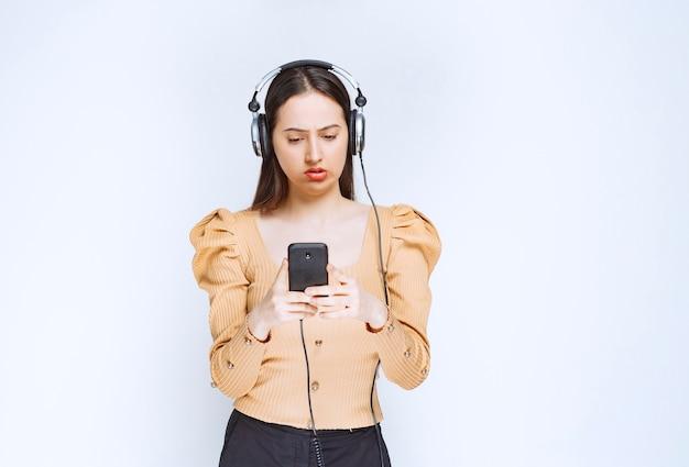 Een aantrekkelijk vrouwenmodel dat muziek in hoofdtelefoons luistert. Premium Foto