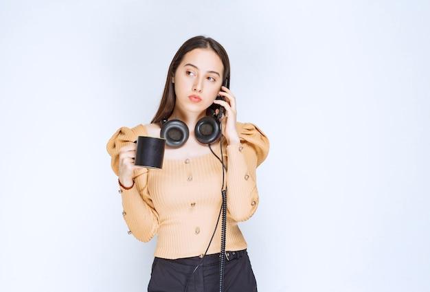 Een aantrekkelijk vrouwenmodel dat op mobiele telefoon spreekt en een kop houdt. Premium Foto