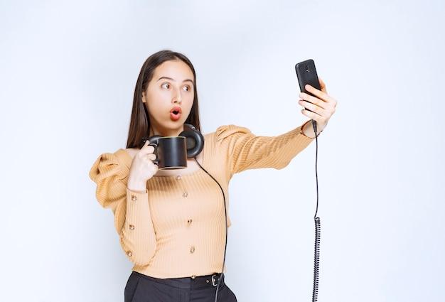 Een aantrekkelijk vrouwenmodel dat selfie neemt met een kopje drank en een koptelefoon.