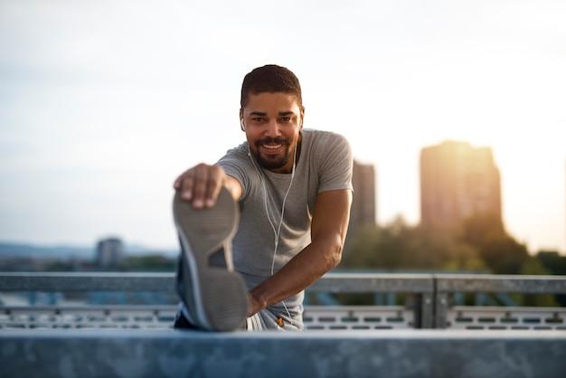 Een aantrekkelijke atleet die de benen strekt en zich voorbereidt op looptraining