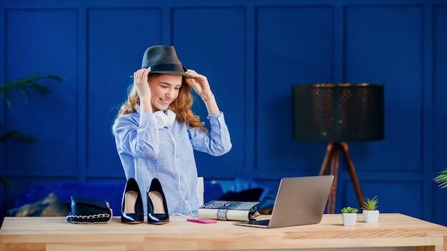 Een aantrekkelijke blanke vrouwelijke blogger probeert een stijlvolle hoed tijdens het opnemen van een blogvideo.