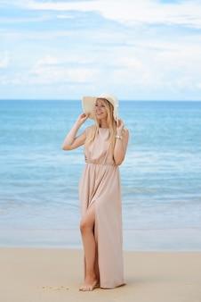Een aantrekkelijke blonde jonge vrouw in een hoed en een lange jurk staat