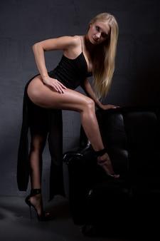 Een aantrekkelijke blondine in een elegante avondjurk met een grote split boven de heup