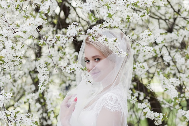 Een aantrekkelijke bruid in een kanten jurk en een sluier glimlacht bij de bloeiende bomen in het park