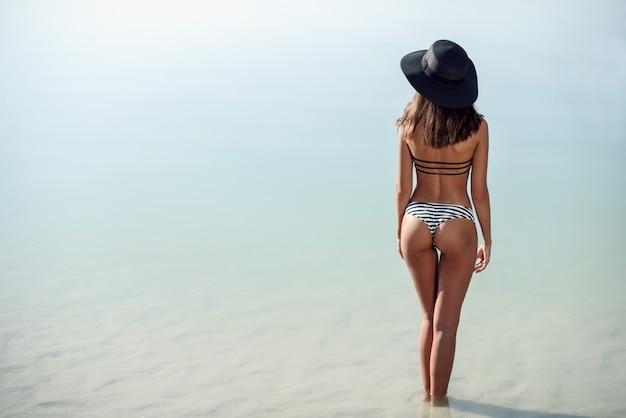 Een aantrekkelijke gebruinde vrouw met een getraind perfect lichaam in een bikini en hoed op het strand. mooi geschiktheidsmeisje. zomervakantie concept. onherkenbaar meisje aan de kust.