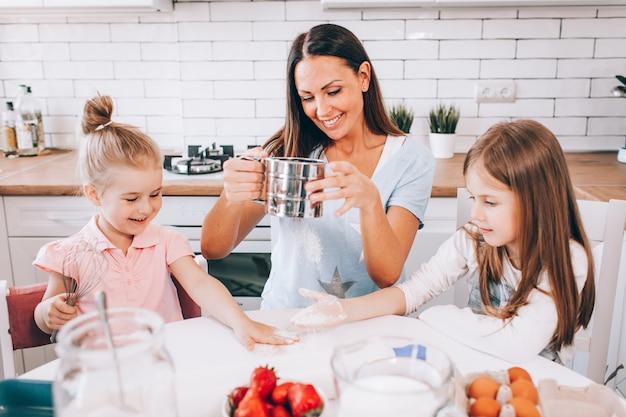 Een aantrekkelijke glimlachende familie van moeder, en twee dochters die thuis in een lichte keuken bakken.