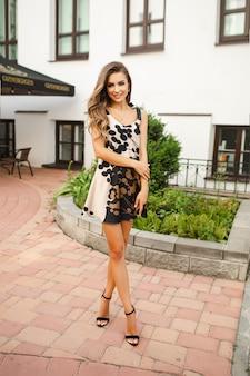 Een aantrekkelijke jonge blanke vrouw in korte jurk en schoenen met een tas die poseert voor de camera in de buurt van het prachtige gebouw