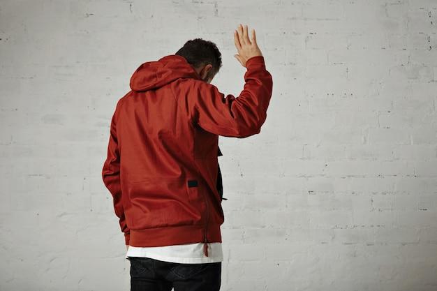 Een aantrekkelijke jonge man in een rood jasje zwaait het portret vanaf de achterkant op een witte muur vaarwel