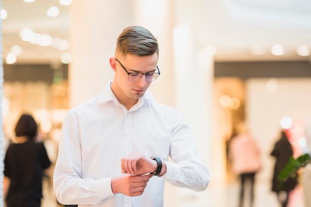 Een aantrekkelijke jonge man in wit overhemd zoekt zijn polshorloge; de tijd controleren