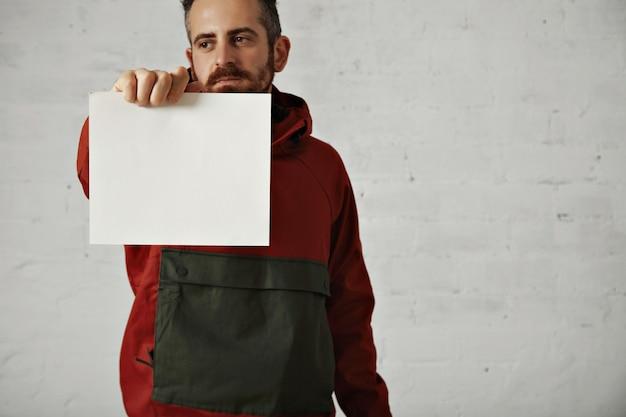 Een aantrekkelijke jonge man met donker haar, donkere ogen en een baard laat een leeg wit vel papier zien dat op wit wordt geïsoleerd