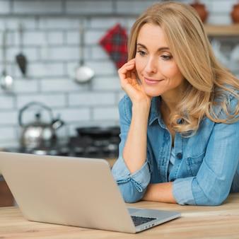 Een aantrekkelijke jonge onderneemster die laptop op houten lijst bekijkt