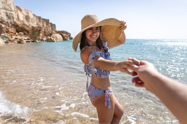 Een aantrekkelijke jonge vrouw aan de kust in een zwempak en een grote hoed loopt bij de hand met een man. Premium Foto