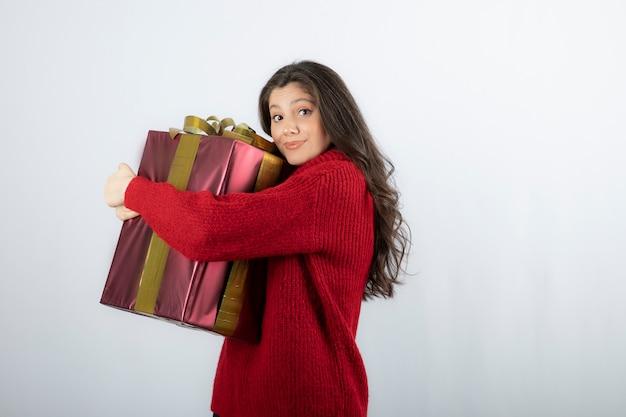 Een aantrekkelijke jonge vrouw die een kerstcadeau omhelst over een witte muur.