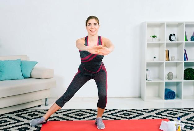 Een aantrekkelijke jonge vrouw die geschiktheidsoefening in de woonkamer doet
