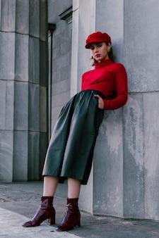Een aantrekkelijke jonge vrouw die op muur leunt met dient haar zak in