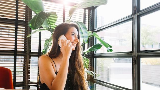 Een aantrekkelijke jonge vrouw die op slimme telefoon spreekt