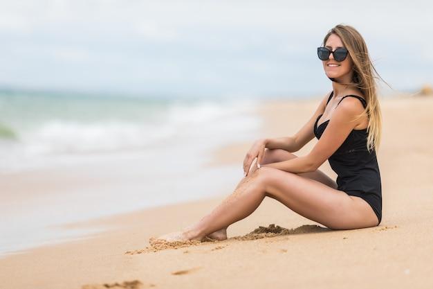Een aantrekkelijke jonge vrouw in een zwarte bikini zit op een strand met haar elleboog op haar knie