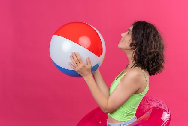Een aantrekkelijke jonge vrouw met kort haar in een groene crop top met opblaasbare bal te kijken naar de zijkant op een roze achtergrond