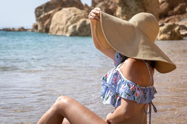 Een aantrekkelijke jonge vrouw zit aan de kust in een zwempak en een grote hoed en zonnebaadt.