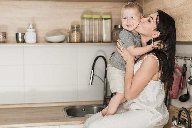 Een aantrekkelijke jonge vrouw zittend op de aanrecht liefdevolle haar zoon