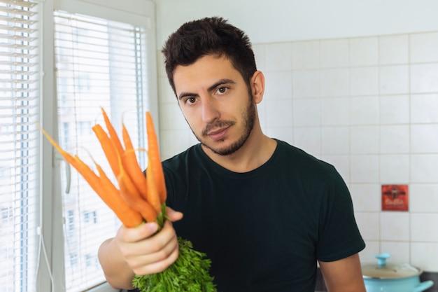 Een aantrekkelijke jongeman houdt een verse biologische wortel in zijn handen. biedt haar smaak.
