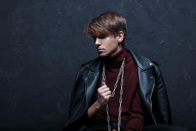 Een aantrekkelijke jongeman in een leren jack in warme bordeauxrode golf met een metalen zilveren ketting om zijn nek, poseren in een donkere studio tegen een zwarte muur. leuke mode-man