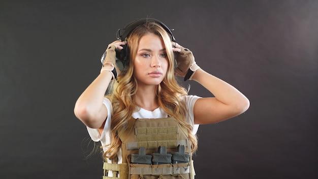Een aantrekkelijke legervrouw gekleed in een militaire platendrager op een wit t-shirt met rook.