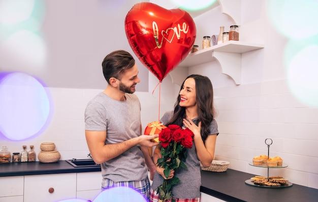 Een aantrekkelijke man en een knappe vrouw in huiskleding staan in de keuken en glimlachen terwijl ze elkaar cadeautjes geven op valentijnsdag.