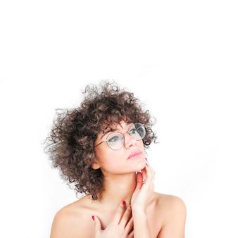 Een aantrekkelijke vrouw die bril draagt wat betreft haar wang die over witte achtergrond wordt geïsoleerd