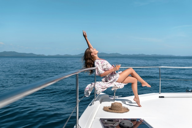 Een aantrekkelijke vrouw die martini-cocktail op het luxejacht drinkt. concept over vrije tijd, zomervakanties. kopieer ruimte