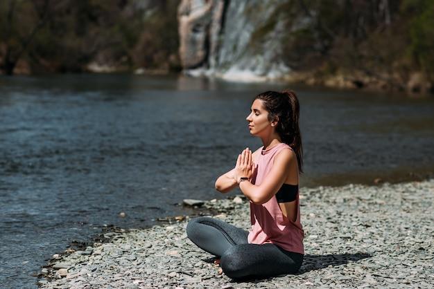 Een aantrekkelijke vrouw doet yoga. gezonde levensstijl. lichaamsconcentratie. een vrouw doet yoga bij het meer. een meisje doet yoga bij zonsopgang. een vrouw mediteert in de natuur. bergmeer meditatie. detailopname