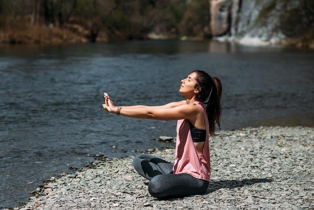 Een aantrekkelijke vrouw doet yoga. gezonde levensstijl. lichaamsconcentratie. een vrouw doet yoga bij het meer. een meisje doet yoga bij zonsopgang. een vrouw mediteert in de natuur. bergmeer meditatie. ruimte kopiëren