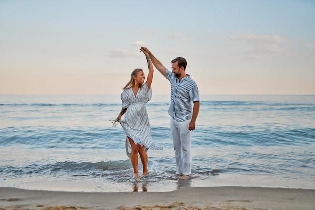 Een aantrekkelijke vrouw in een jurk en een knappe bebaarde man in een overhemd en een witte broek dansen verliefd op de kust, met plezier op vakantie.