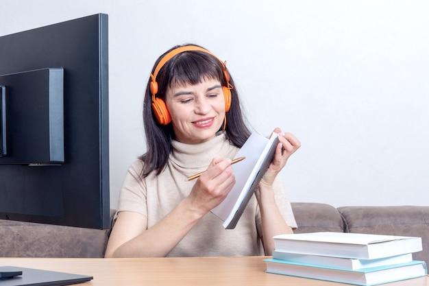Een aantrekkelijke vrouwelijke leraar in oranje hoofdtelefoons die achter een computermonitor zit, legt een onlinetaak uit, met een notitieboekje.