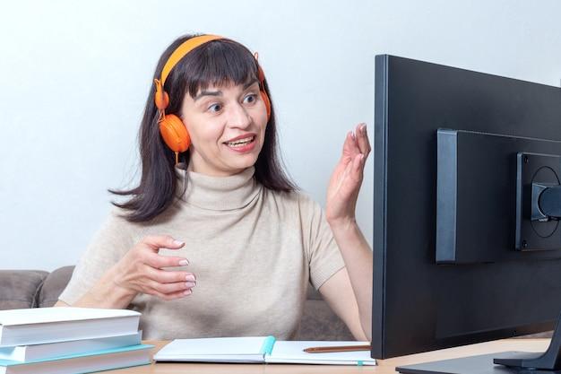 Een aantrekkelijke vrouwelijke leraar in oranje koptelefoon zit achter een computermonitor, legt een onlinetaak uit. online leerconcept