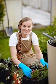 Een aantrekkelijke vrouwelijke tuinman maakt bloemen klaar voor verplanten in de tuin.