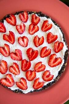 Een aardbeien cheesecake versierd met hartvormige aardbeien ligt op een koraalkleurig bord en staat op een groen servet. illustratie van een cheesecake recept met aardbeien. uitzicht van boven.