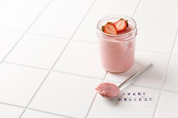 Een aardbeiendessertmousse in glas met lepel op wit bord op witte tegelachtergrond