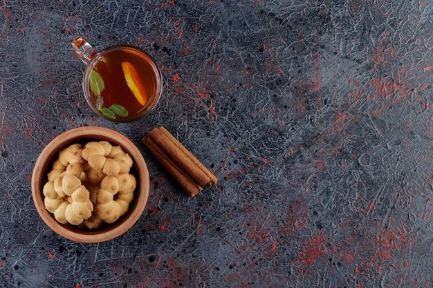 Een aarden kom cupcakes rond met een gat en een glazen kop hete thee.