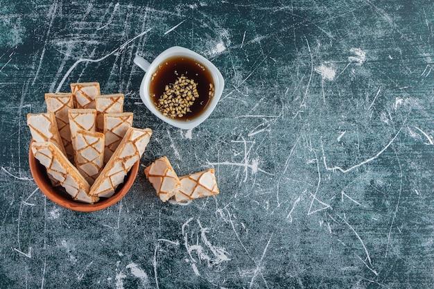 Een aarden kom vol zoete wafelstokjes met een kopje zwarte thee.