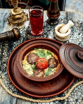 Een aardewerk pan met gehaktballetjes gekookt in ei met spinazie