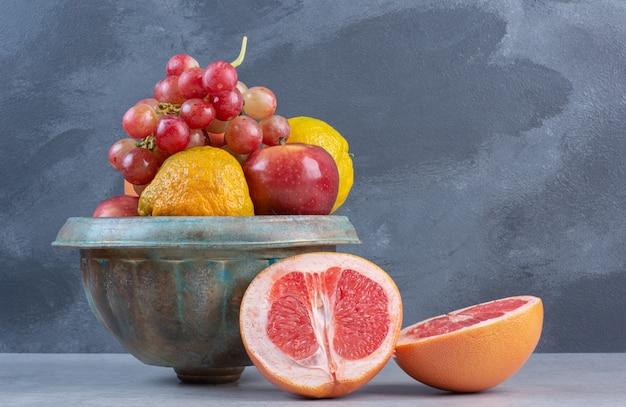 Een aardewerk vol vers biologisch fruit. op grijze achtergrond.
